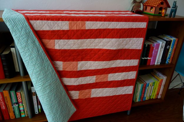 A cheerful coral and pale pink crib quilt with salmon accents. Maggie has a aqua honeycomb patterned backing and coral double binding.